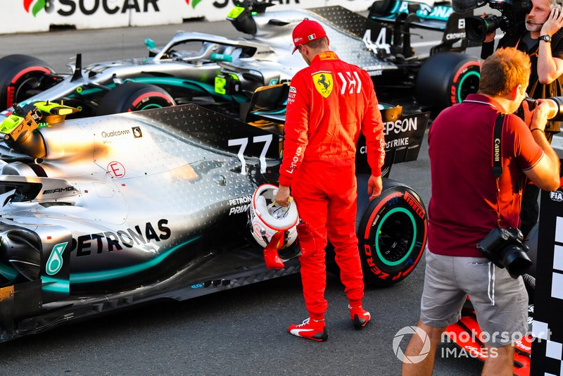 Sebastian Vettel, Ferrari, inspects the car of pole man Valtteri Bottas, Mercedes AMG W10, after Qualifying