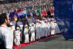 Los pilotos y los niños escuchan el himno nacional