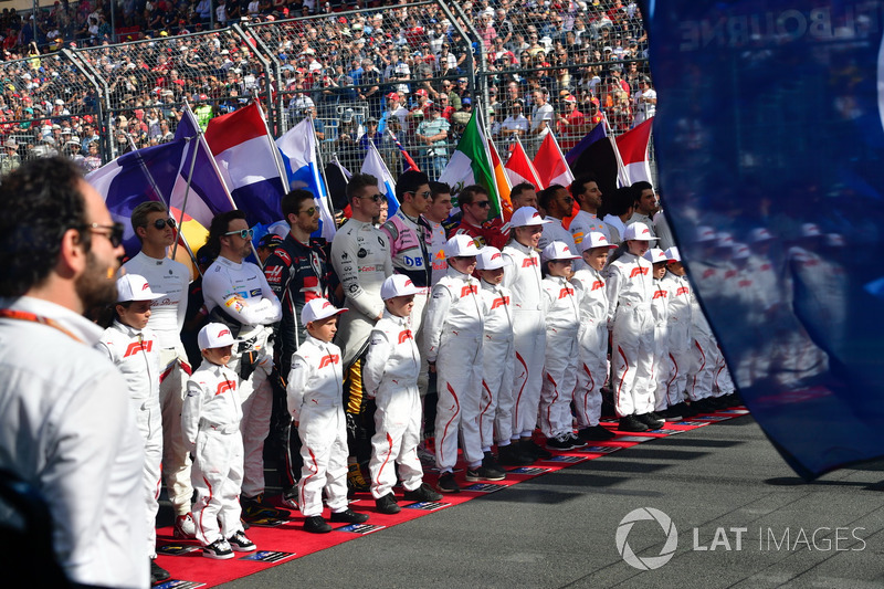 Drivers and grid kids observe the National Anthem on the grid