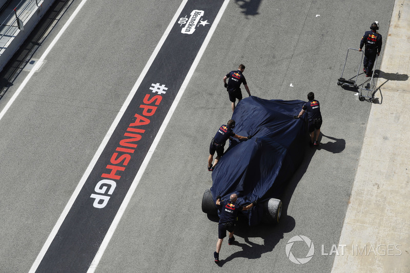Mechanics push the damaged Daniel Ricciardo Red Bull Racing RB14 under covers in the pit lane