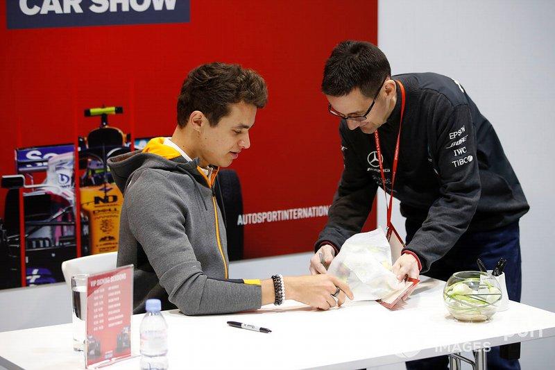 Lando Norris, McLaren signs a miniature replica helmet for a fan