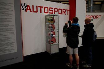 Fans take photographs of helmets on the Autosport stand
