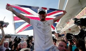 Lewis Hamilton, Mercedes AMG F1, lifts a Union Flag after winning the world championship