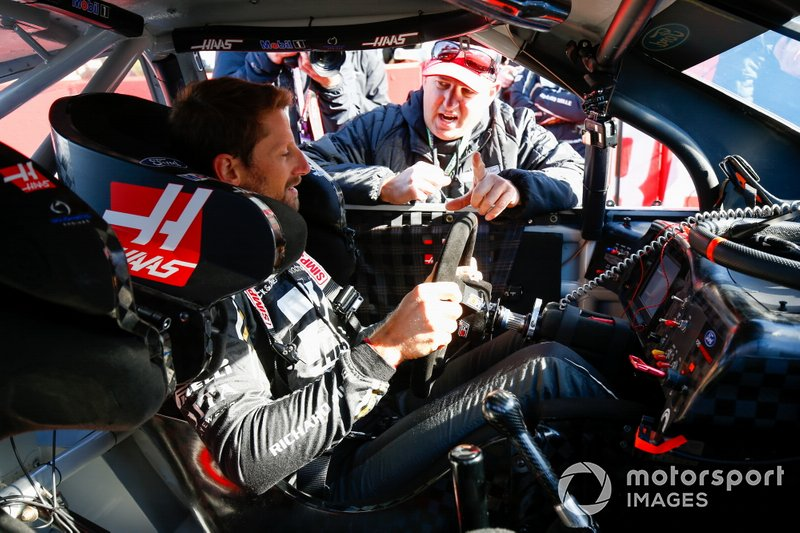 Romain Grosjean, Haas F1 Team VF-19, gets into the car of NASCAR Cup driver Tony Stewart
