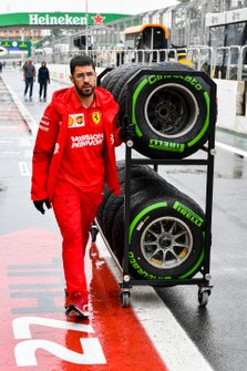 Ferrari mechanic with Pirelli tyres in the pit lane