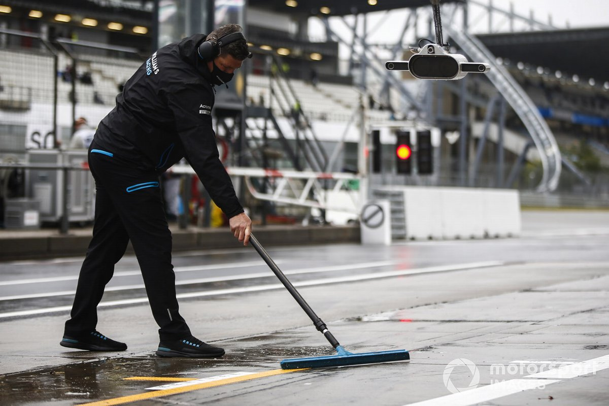 A member of the Williams Racing team shifts water in the pitlane