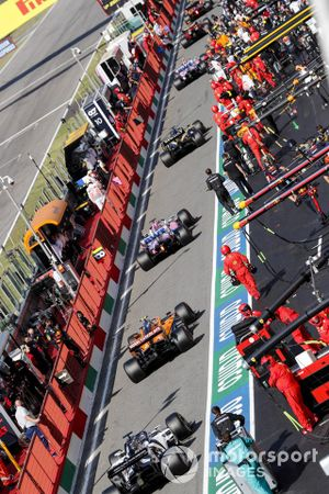 Daniil Kvyat, AlphaTauri AT01, Lando Norris, McLaren MCL35 and Sergio Perez, Racing Point RP20 in the pit lane