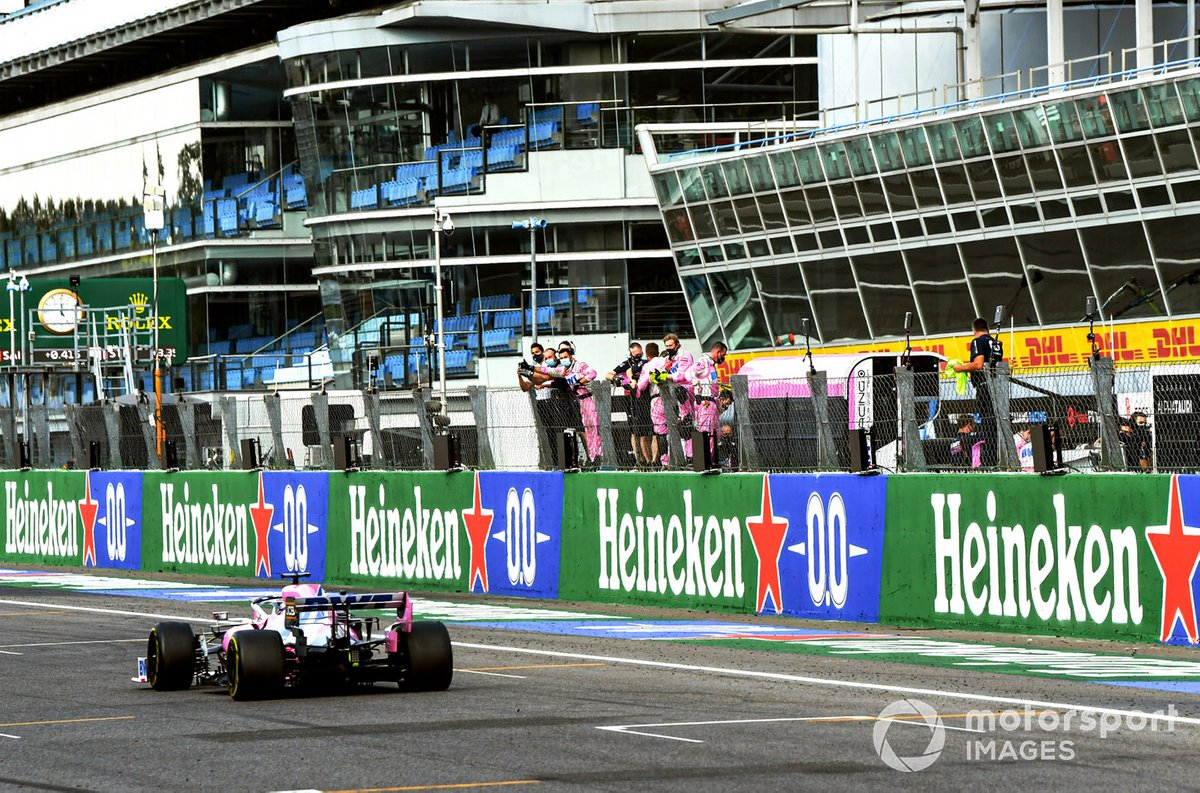 Sergio Perez, Racing Point RP20, passes his team on the pit wall at the end of the race
