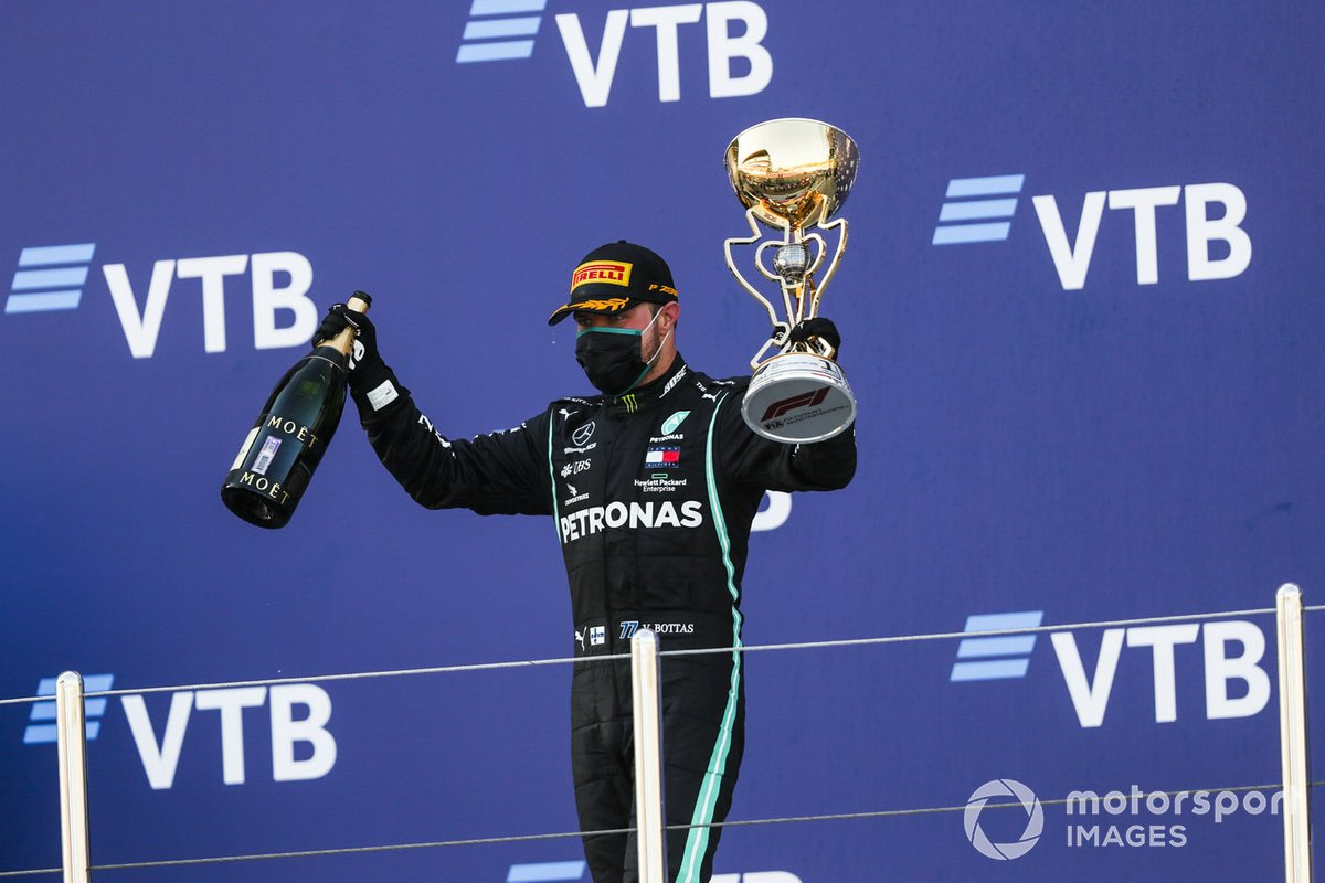 il vincitore Mercedes-AMG F1 festeggia la vittoria sul podio con lo champagne e il trofeo