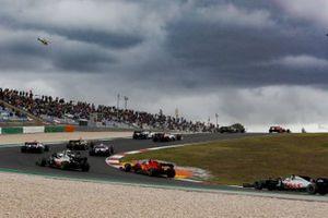 Romain Grosjean, Haas VF-20, Sebastian Vettel, Ferrari SF1000, and Kevin Magnussen, Haas VF-20, chase the pack on the opening lap