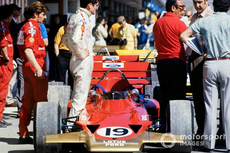 John Miles stands beside his Lotus 72 Ford in the pit lane