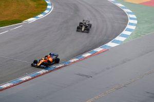 Carlos Sainz Jr., McLaren MCL34, leads Kevin Magnussen, Haas F1 Team VF-19