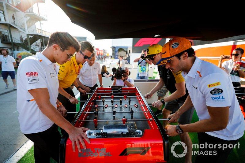 Lando Norris, McLaren, Carlos Sainz Jr, McLaren y Nico Hulkenberg, del equipo Renault F1, juegan al futbolito en el paddock.