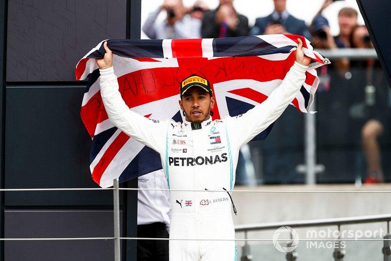 Il vincitore della gara Lewis Hamilton, Mercedes AMG F1, festeggia sul podio con una bandiera