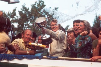 Race winner Ronnie Peterson, Team Lotus celebrates on the podium with team boss Colin Chapman