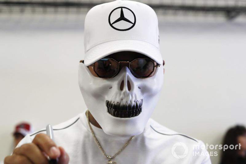 Lewis Hamilton, Mercedes AMG F1, con máscara de calavera, firma autógrafos para jóvenes fanáticos