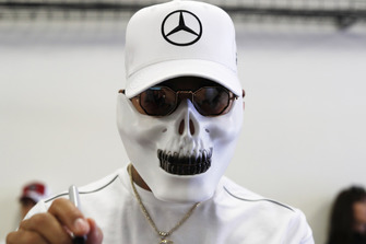 Lewis Hamilton, Mercedes AMG F1, wearing a skull mask, signs autographs for young fans