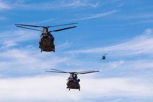 US Army Boeing CH-47F Chinook helicopters boven de grid met Airbus AS350 B£ erachteraan