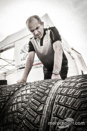 Un meccanico del Team Peugeot Sport Italia con degli pneumatici