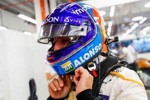 Fernando Alonso, McLaren, adjusts his crash helmet