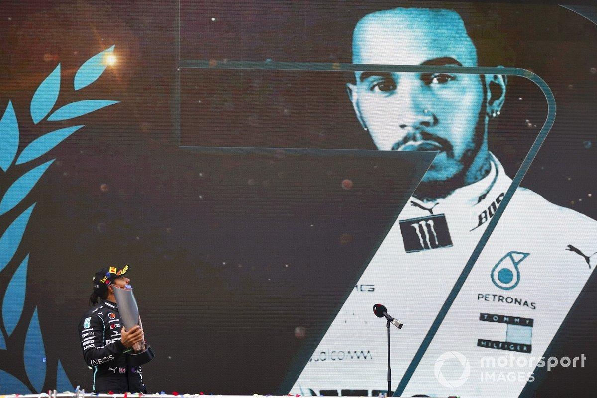 Lewis Hamilton, Mercedes-AMG F1, 1st position, memegang trofi kemenangannya di GP Turki dengan foto dirinya berukuran besar di belakangnya
