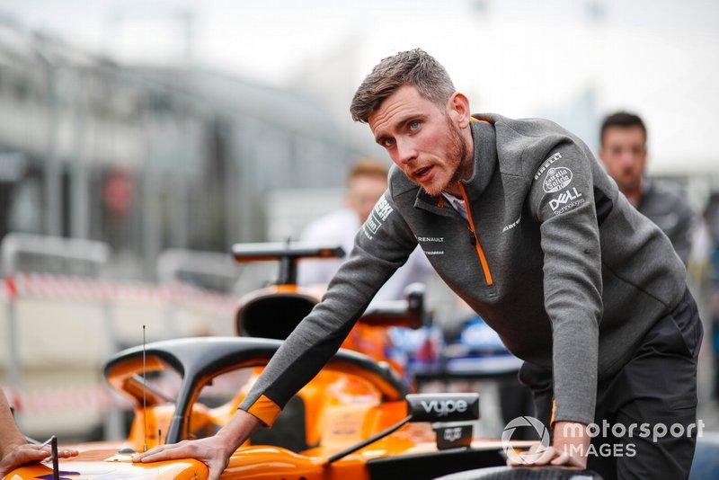 Un ingeniero de McLaren empuja el coche de Carlos Sainz Jr. y McLaren MCL34 por el pit lane