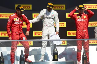 Sebastian Vettel, Ferrari, 2nd position, Lewis Hamilton, Mercedes AMG F1, 1st position, and Charles Leclerc, Ferrari, 3rd position, on the podium