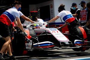 I meccanici della Haas, riportano l'auto di Mick Schumacher, Haas VF-21, nel garage