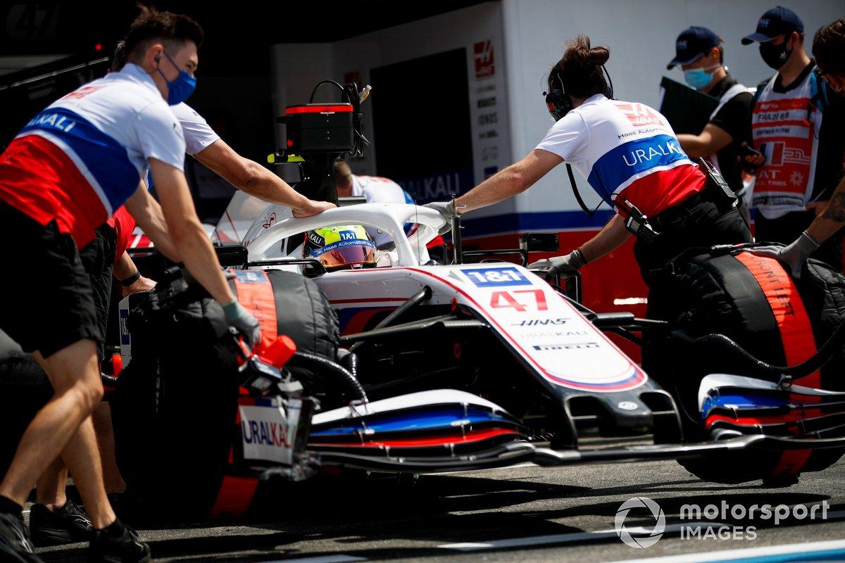 Haas F1 mechanics return Mick Schumacher, Haas VF-21, to the garage