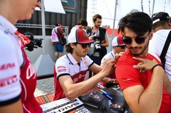 Antonio Giovinazzi, Alfa Romeo Racing, and Kimi Raikkonen, Alfa Romeo Racing, sign autographs for fans