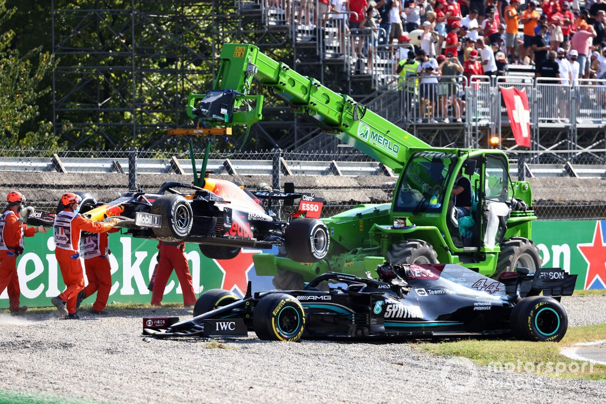 Los oficiales de pista retiran de la grava los coches de Max Verstappen, Red Bull Racing RB16B, y Lewis Hamilton, Mercedes W12