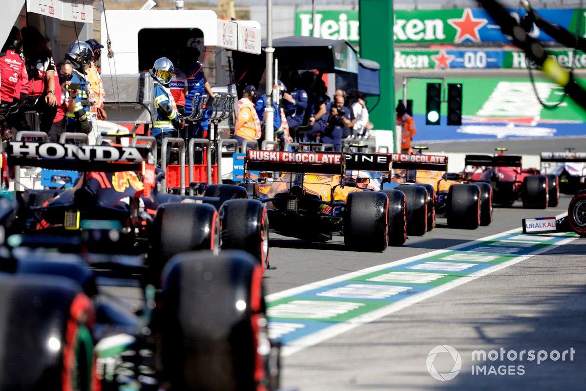 Daniel Ricciardo, McLaren MCL35M, y Sergio Perez, Red Bull Racing RB16B, en la cola del pit lane