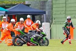 Oficiales empujan la moto de Tom Sykes Kawasaki Racing Team, después de una caída