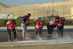 Marshals clear the oil from the track