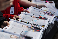 Fans present programmes to be signed by drivers