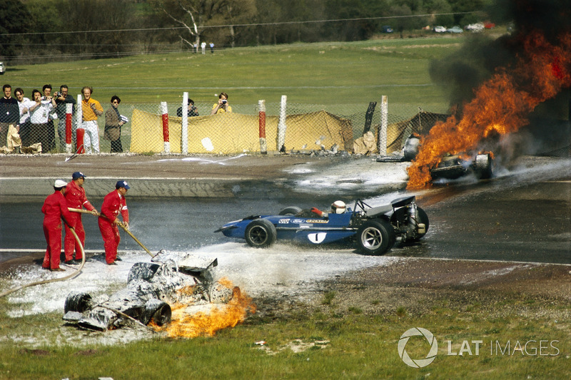 Jackie Oliver's BRM collided with Jacky Ickx's Ferrari. Jackie Stewart is passing the scene of accid