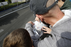Spectator reading a newspaper with Joel Eriksson, Motopark Dallara F317 - Volkswagen