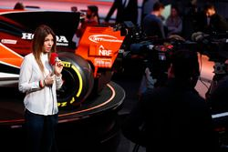 A reporter is filmed in front of the McLaren MCL32