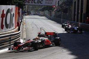 Lewis Hamilton, McLaren MP4-26 Mercedes, voor Sebastien Buemi, Toro Rosso STR6 Ferrari, en Narain Karthikeyan, HRT F111 Cosworth