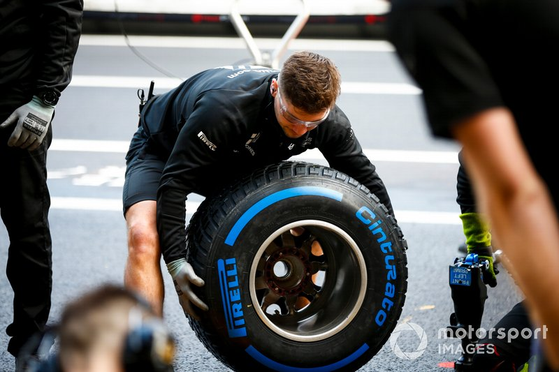 Haas F1 mechanic with Pirelli tyre during pit stop practice
