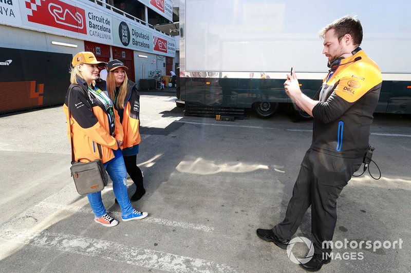 A McLaren team member takes a photo of two fans