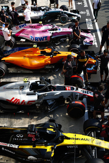Cars of Nico Hulkenberg, Renault Sport F1 Team RS 18, Kevin Magnussen, Haas F1 Team VF-18, Lando Norris, McLaren MCL33, Esteban Ocon, Racing Point Force India VJM11, and Lewis Hamilton, Mercedes AMG F1 W09, line up in the pit lane