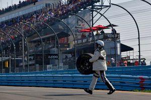 Un oficial de NASCAR recupera una rueda suelta