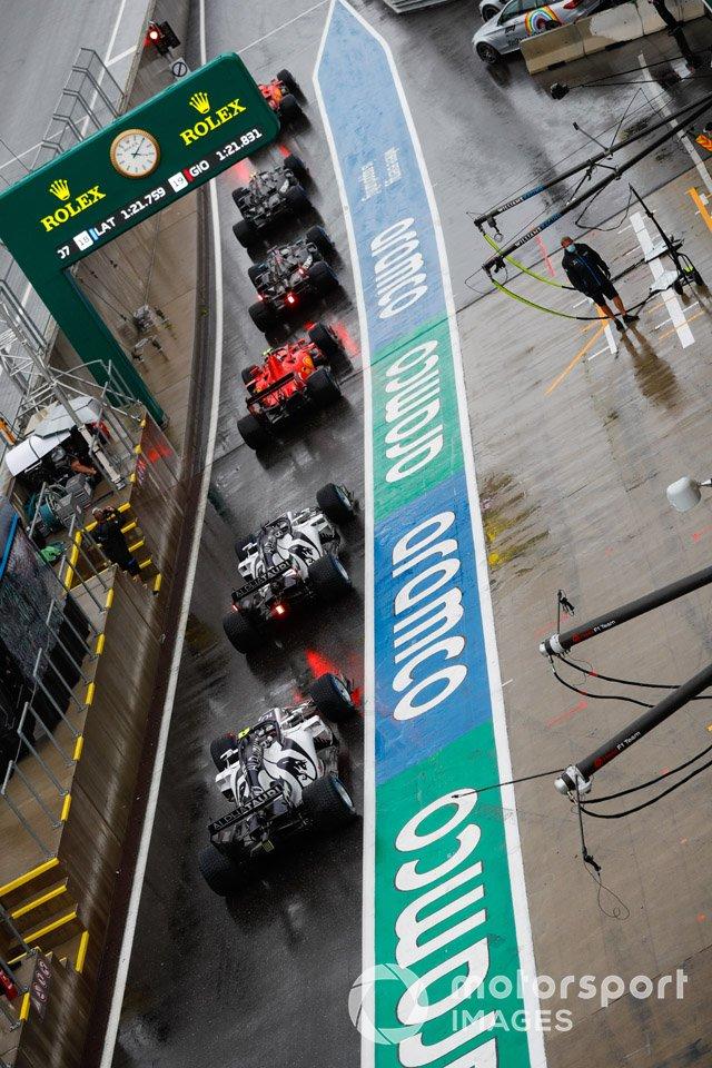 Pierre Gasly, AlphaTauri AT01, se encuentra en la parte trasera de una fila de coches en el pit lane, siendo Daniil Kvyat, AlphaTauri AT01 y un Ferrari