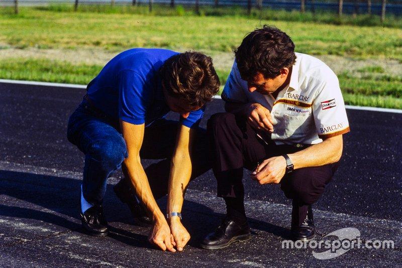 Gerhard Berger examina el estado del asfalto con Jackie Oliver
