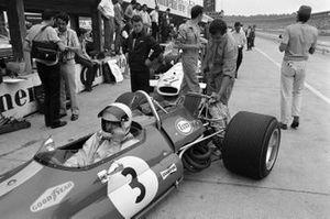 Mechanics work on the rear of Jack Brabham's Brabham BT33 Ford