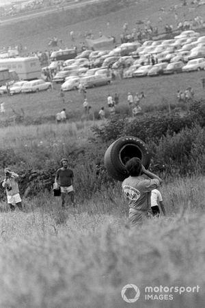 Un oficial de pista retira la rueda perdida de Jackie Stewart que causó su retiro en la vuelta 35