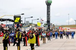 Drivers and crew stand for the national anthem