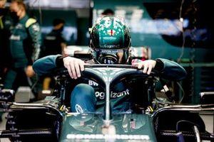 Lance Stroll, Aston Martin, climbs into his car in the garage