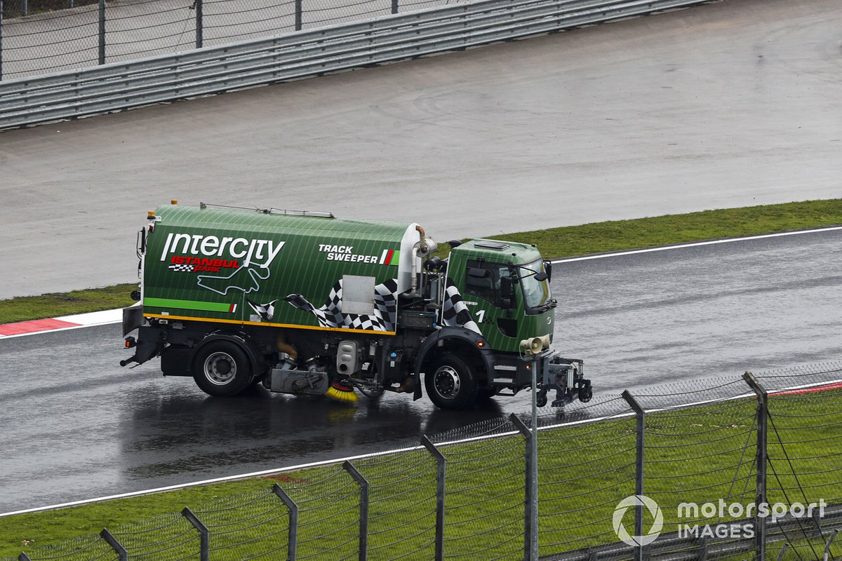 Un barredor de pista intenta limpiar el agua del circuito